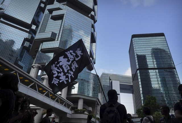 A demonstrator carries a flag reading Liberate Hong Kong, Revolution of Our Times outside the High Court in Hong Kong
