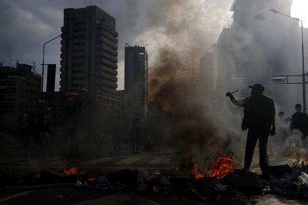 A demonstrator builds a fire on the street during a rally against Venezuela's President Nicolas Maduro's government in Caracas