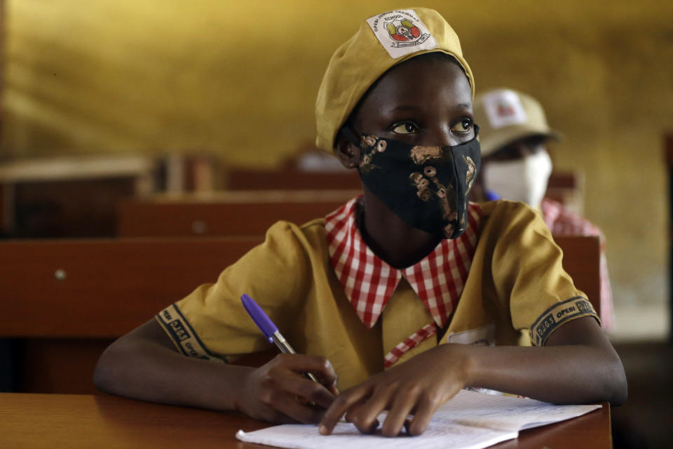 Students from Opebi Junior Grammar School, wearing face masks to protect against coronavirus, attend lessons in Lagos Nigeria, Monday, Jan. 18, 2021. Nigeria officials resumed both public and private schools on Monday for students following months of closure to curb the spread of coronavirus. as cases increase in the country. (AP Photo/Sunday Alamba)