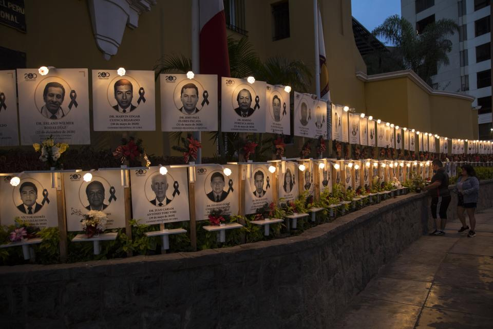 Relatives leave flowers on the portrait of Jorge Luis Casana, 62, a doctor who died due to the new coronavirus in Lima, Peru, Tuesday, Jan. 19, 2021. The Peruvian Medical College reported that at least 11 doctors have died during the first days of 2021. (AP Photo/Rodrigo Abd)
