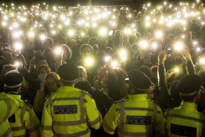 People in the crowd turn on their phone torches as they gather in Clapham Common, London, at the vigil for Sarah Everard