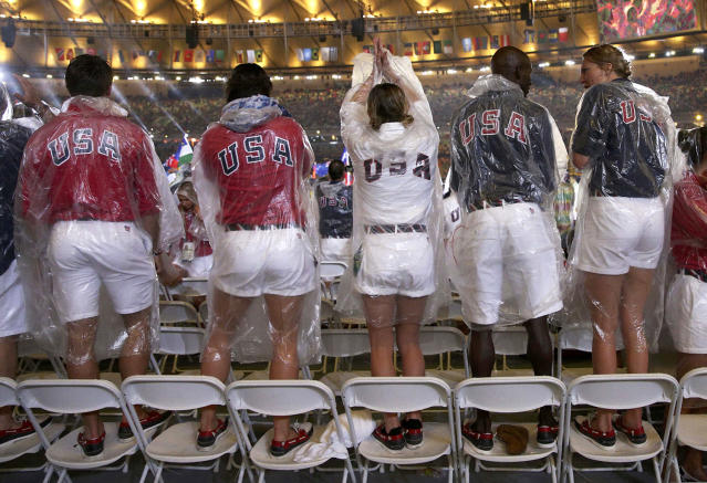 <p>U.S. athletes stand on chairs in the rain during the closing ceremony for the 2016 Rio Olympics. (REUTERS/Stoyan Nenov) </p>