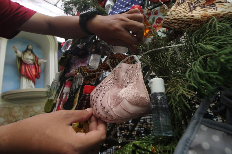 A man decorates a Christmas tree with masks and hand sanitizers at a church in Surabaya