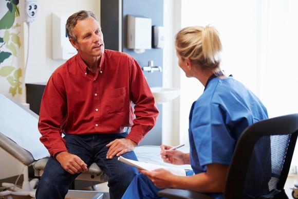 Female doctor talking with male patient in an exam room