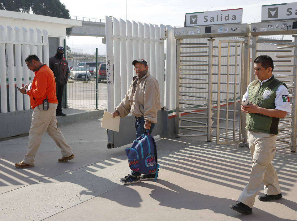 """FILE - In this Jan. 29, 2019, file photo, migrant Carlos Catarldo Gomez, of Honduras, center, is escorted by Mexican officials after leaving the U.S., the first person returned to Mexico to wait for his asylum trial date as part of a new program """"Remain In Mexico"""" policy in Tijuana, Mexico. The Supreme Court has ordered the reinstatement of the policy, saying that the Biden administration likely violated federal law by trying to end the Trump-era program that forces people to wait in Mexico while seeking asylum in the U.S. The decision immediately raised questions about what comes next for the future of the policy, also known as the Migrant Protection Protocols. (AP Photo/Gregory Bull, File)"""