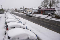 Cars covered in snow at a car dealership in Weeley, southern England, Sunday Feb. 7, 2012. Heavy snow is predicted to bring travel disruption to south-east England as bitterly cold winds grip much of the nation.(Joe Giddens/PA via AP)