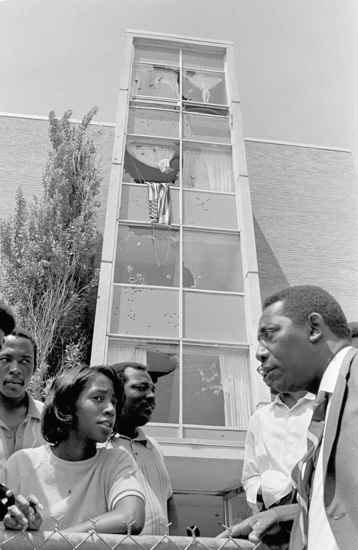 FILE - In this May 15, 1970, file photo, Mayor Charles Evers, of Fayette, Miss., a civil rights leader, talks with students outside the bullet-riddled women's dormitory at Jackson State College, in Jackson, Miss., where two young African-Americans were shot to death by police. More than a half century late, Jackson State University, in Mississippi, is honoring its Class of 1970, on Saturday, May 15, 2021. Commencement was canceled after white law enforcement officers marched onto campus of the historically Black school and violently suppressed protests against racism. (AP Photo, File)