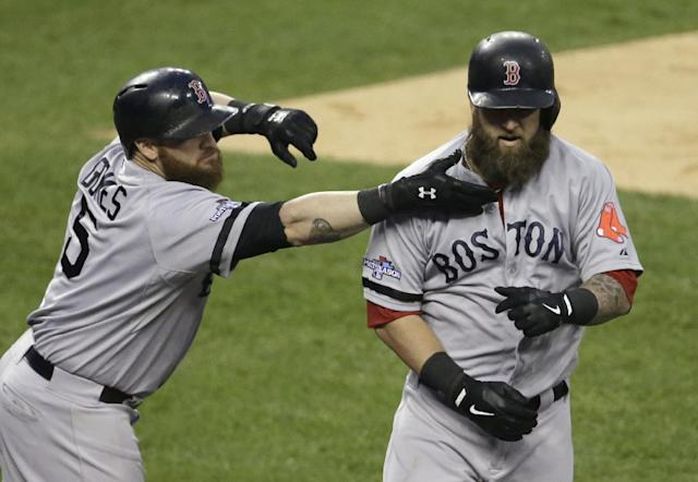 Boston Red Sox's Jonny Gomes reaches to pull the beard of Mike Napoli after Napoli hits a home run in the seventh inning during Game 3 of the American League baseball championship series against the Detroit Tigers Tuesday, Oct. 15, 2013, in Detroit. (AP Photo/Carlos Osorio)