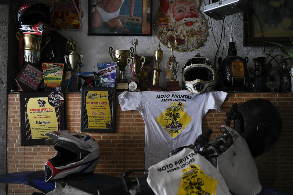 Awards and medals won by motorcycle stuntman Pedro Aldana sit on a wall at his home in the Catia neighborhood of Caracas, Venezuela, Thursday, Jan. 21, 2021. The 33-year-old makes a living with his shows inspiring his young fans who flock to his shop, where he teaches them to change the oil and tune up their bicycles. (AP Photo/Matias Delacroix)