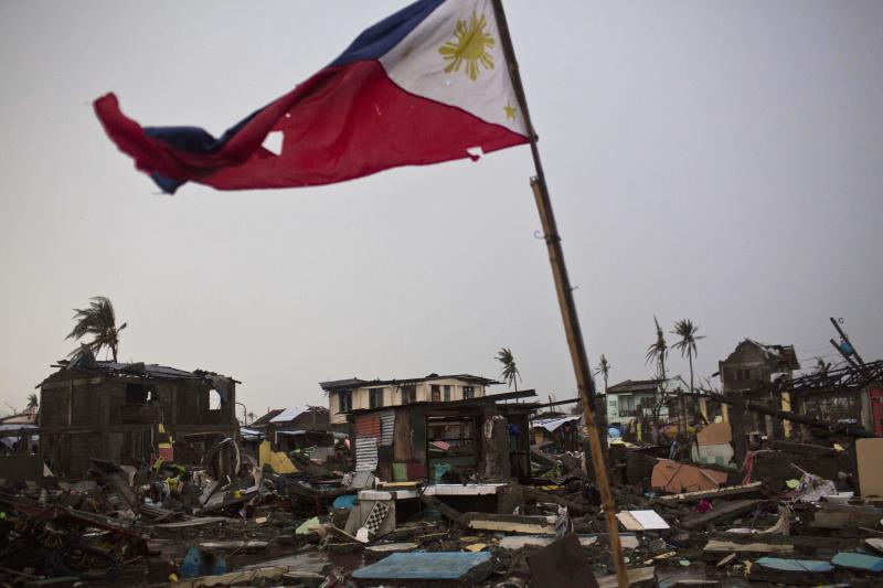 FILE - In this Friday Nov. 22, 2013 file photo, a flag of the Philippines flies over a destroyed neighborhood in Tacloban, Philippines. U.S. author Mitch Albom has launched a drive to rebuild 10 libraries in Tacloban, a central Philippine city ravaged by Typhoon Haiyan in November. National Book Store Foundation, his Philippine partner in the project, said Tuesday that Albom has pledged to raise $160,000, starting with his own contribution of $10,000 for the libraries. (AP Photo/David Guttenfelder, File)