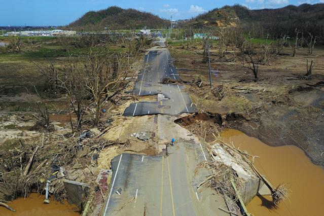 <p>A man rides his bicycle through a damaged road in Toa Alta, west of San Juan, Puerto Rico, on September 24, 2017 following the passage of Hurricane Maria. Authorities in Puerto Rico rushed on September 23, 2017 to evacuate people living downriver from a dam said to be in danger of collapsing because of flooding from Hurricane Maria. (Photo: Ricardo Arduengo/AFP/Getty Images) </p>