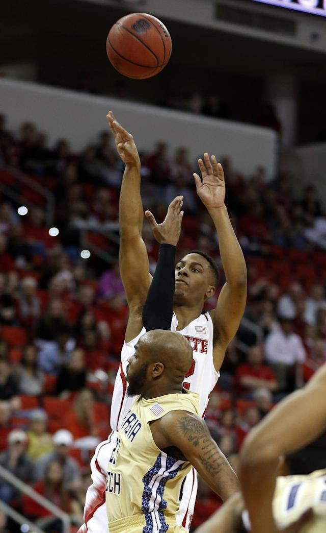 North Carolina State's Ralston Turner (22) shoots over the defense of Georgia Tech's Trae Golden (23) during the first half of an NCAA college basketball game at PNC Arena in Raleigh, N.C., Sunday, Jan. 26, 2014. (AP Photo/The News & Observer, Ethan Hyman)