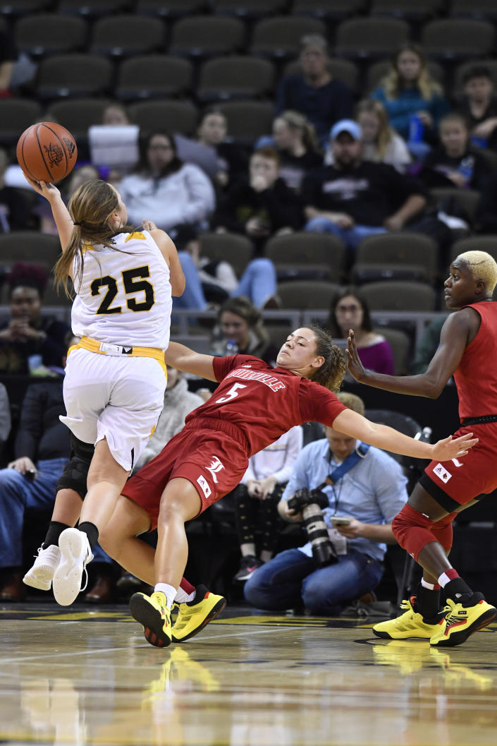 Louisville guard Mykasa Robinson (5) takes a charge from Northern Kentucky guard Ally Niece (25) during the second half of an NCAA college basketball game in Highland Heights, Ky., Sunday, Dec. 8, 2019. Louisville won 85-57. (AP Photo/Timothy D. Easley)