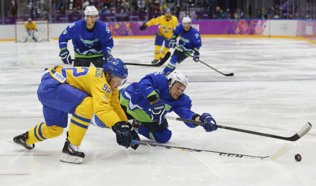 Sweden forward Gabriel Landeskog, left, and Slovenia forward Jan Urbas vie for the puck in the second period of a men's quarterfinal ice hockey game at the 2014 Winter Olympics, Wednesday, Feb. 19, 2014, in Sochi, Russia. (AP Photo/Julio Cortez)