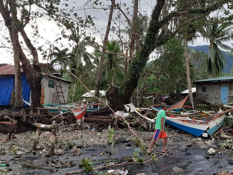 A man walks past storm debris in Biliran