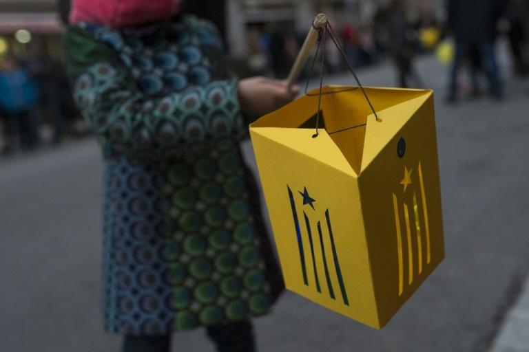 A girl holds a paper lantern cut-out of an Estelada, a Catalan Pro-independence flag during the Three Wise Men Parade (