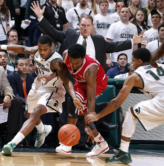 Michigan State's Keith Appling, left, Indiana's Stanford Robinson, center, and Michigan State's Gary Harris, right, fight for a loose ball during the first half of an NCAA college basketball game, Tuesday, Jan. 21, 2014, in East Lansing, Mich. At rear center is Michigan State coach Tom Izzo. Michigan State won 71-66. (AP Photo/Al Goldis)