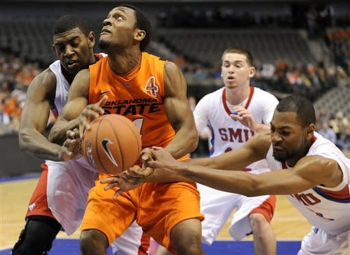 Oklahoma St guard Brian Williams (4) goes to the basket between SMU forward Leslee Smith, left, and forward Shawn Williams (2) in the first half of an NCAA basketball game in Dallas, Wednesday, Dec. 28, 2011. (AP Photo/Matt Strasen)