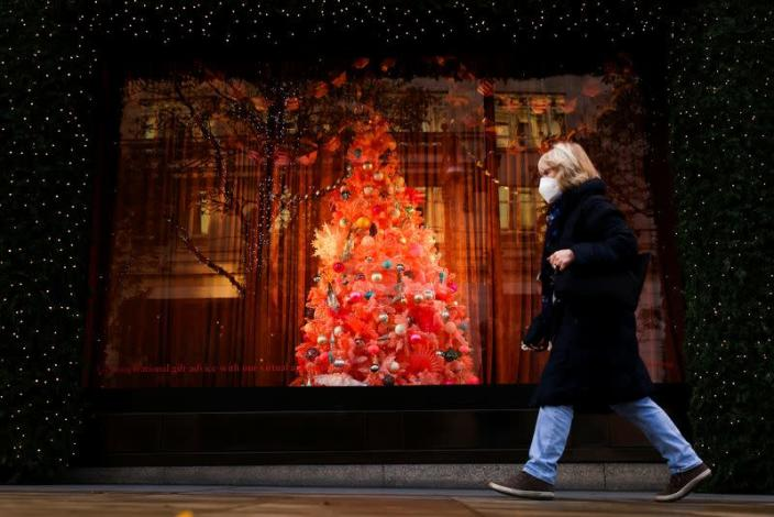 A pedestrian walks past a Christmas tree in a window display at Selfridges department store on Oxford Street amid the coronavirus disease (COVID-19) outbreak in London