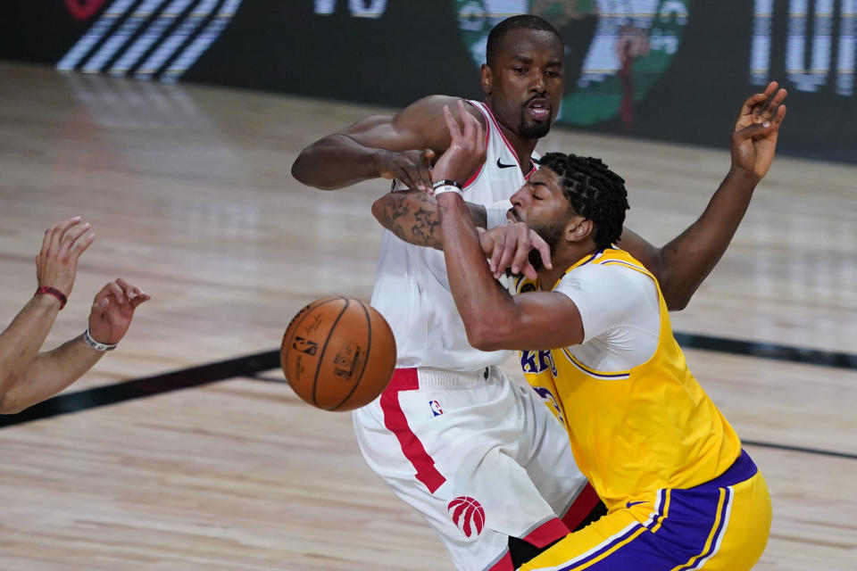 Los Angeles Lakers' Anthony Davis, right, drives into Toronto Raptors' Serge Ibaka (9) during the second half of an NBA basketball game Saturday, Aug. 1, 2020, in Lake Buena Vista, Fla. (AP Photo/Ashley Landis, Pool)