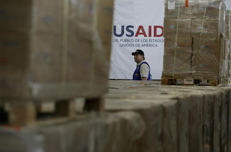 A man walks past boxes of USAID humanitarian aid at a warehouse at the Tienditas International Brigde on the outskirts of Cucuta, Colombia, Thursday, Feb. 21, 2019, on the border with Venezuela. Venezuela's President Nicolas Maduro said he's weighing whether to shut down the border with Colombia, where the bulk of aid meant for Venezuela is being stockpiled and exiled leaders have been gathering ahead of a fundraising concert Friday. (AP Photo/Fernando Vergara)