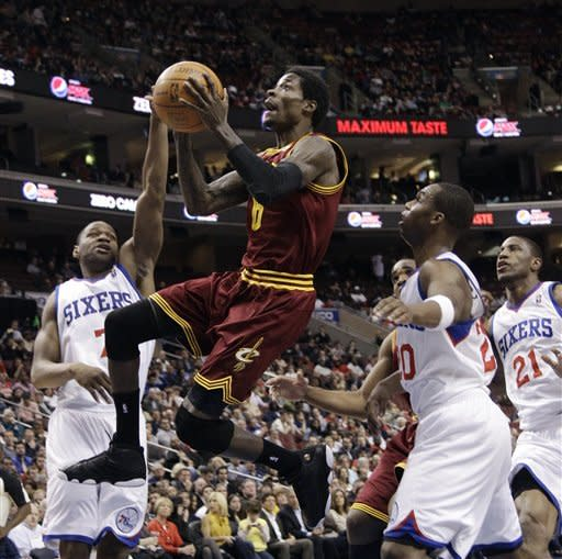 Cleveland Cavaliers' Manny Harris, center, goes up for a shot as Philadelphia 76ers' Sam Young, Jodie Meeks and Thaddeus Young, from left, defend in the first half of an NBA basketball game, Tuesday, March 27, 2012, in Philadelphia. (AP Photo/Matt Slocum)