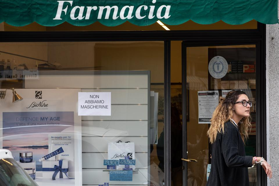 CASALPUSTERLENGO, ITALY - FEBRUARY 23: A young woman stands in front of a pharmacy with a sign on the window reading 'Face masks are over' on February 23, 2020 in Casalpusterlengo, south-west Milan, Italy. Casalpusterlengo is one of the ten small towns placed under lockdown earlier this morning as a second death from coronavirus sparked fears throughout the Lombardy region. (Photo by Emanuele Cremaschi/Getty Images)