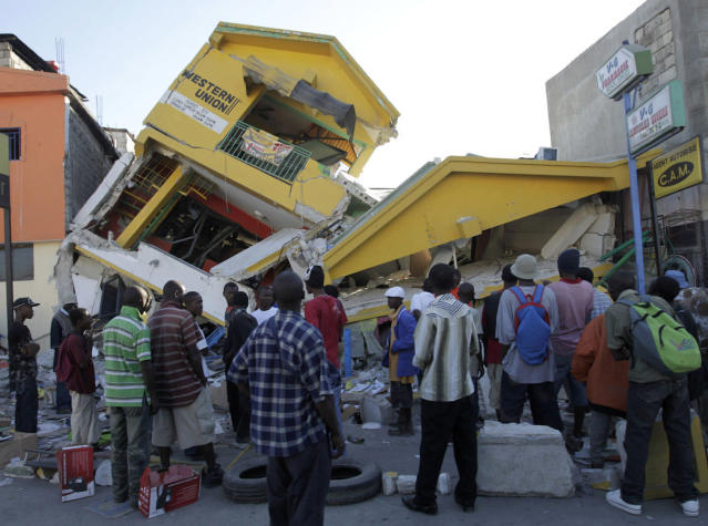 <p>People look at a destroyed building in Port-au-Prince, Haiti, Jan.14, 2010. (Photo: Jorge Silva/Reuters) </p>