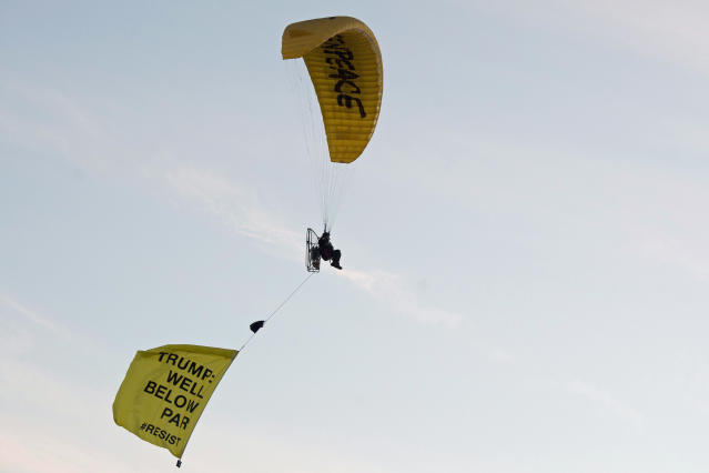 """<p>A Greenpeace protester flying a microlight paraglider-style aircraft passes over President Trump's golf resort in Turnberry, South Ayrshire, with a banner reading """"Trump: Well Below Par"""" shortly after the president arrived at the hotel. (Photo: John Linton/PA Images via Getty Images) </p>"""