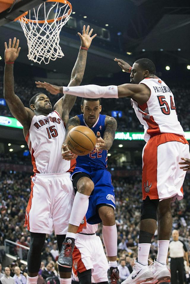 Los Angeles Clippers' Matt Barns, center, looks to pass between Toronto Raptors' Amir Johnston, left, and Patrick Patterson during the first half of an NBA basketball game, Saturday, Jan. 25, 2014 in Toronto. (AP Photo/The Canadian Press, Chris Young)