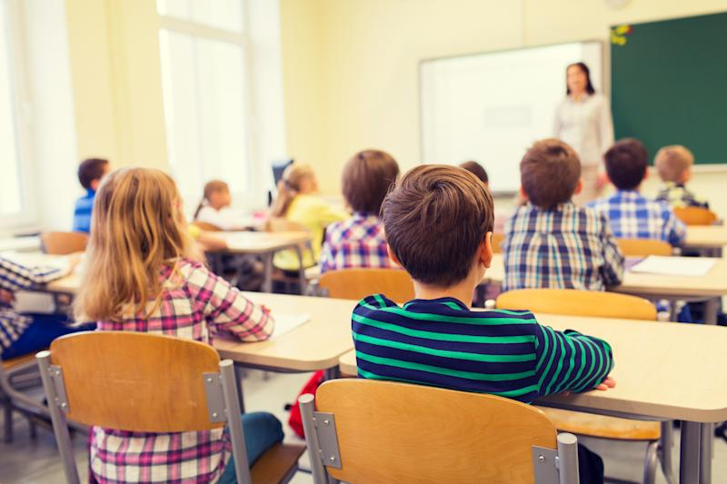 education, elementary school, learning and people concept - group of school kids sitting and listening to teacher in classroom from back