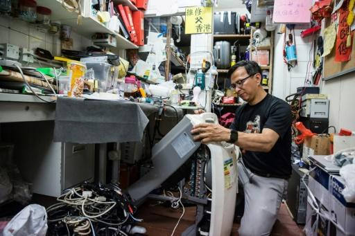 Volunteer electrician Alung Wong repairing a dehumidifier at the headquarters of Fixing Hong Kong