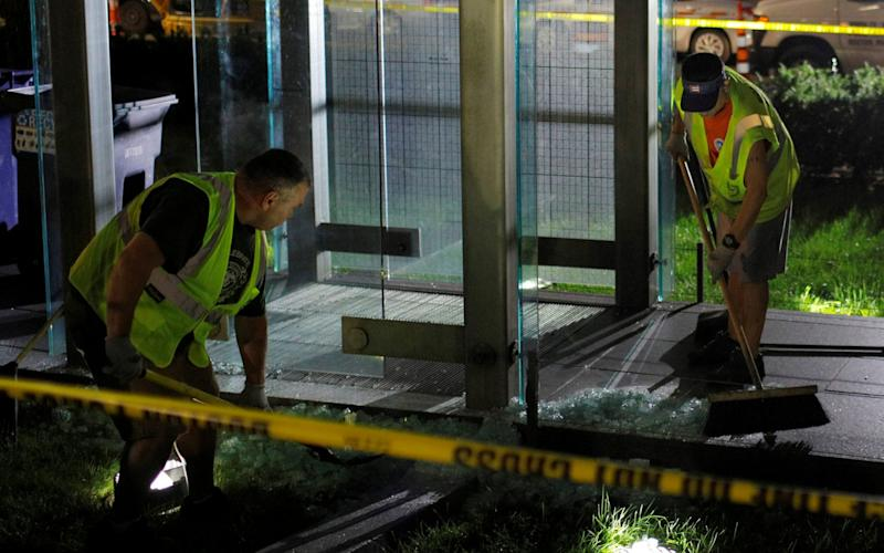 Workers clean up broken glass after the Holocaust Memorial was vandalised in Boston - REUTERS