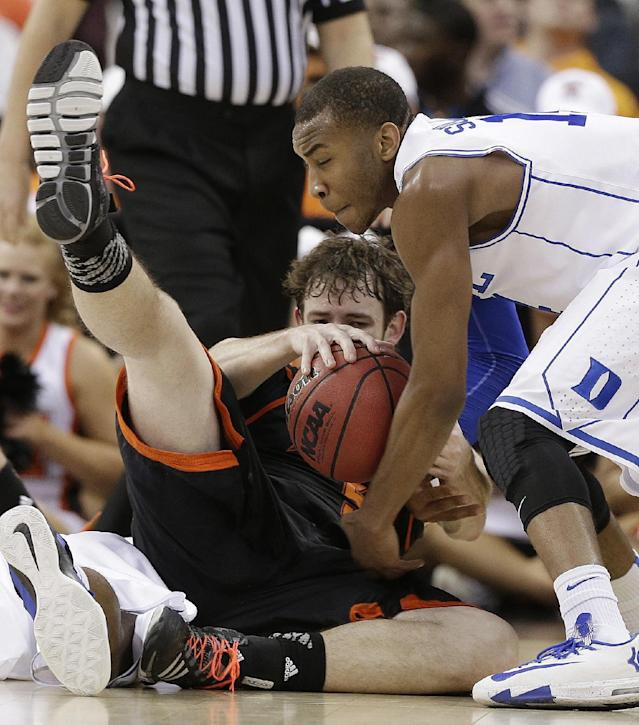 Mercer forward Bud Thomas (5) and Duke guard Rasheed Sulaimon, right, struggle for the ball during the second half of a second-round game in the NCAA college basketball tournament, Friday, March 21, 2014, in Raleigh, N.C. Mercer won 78-71