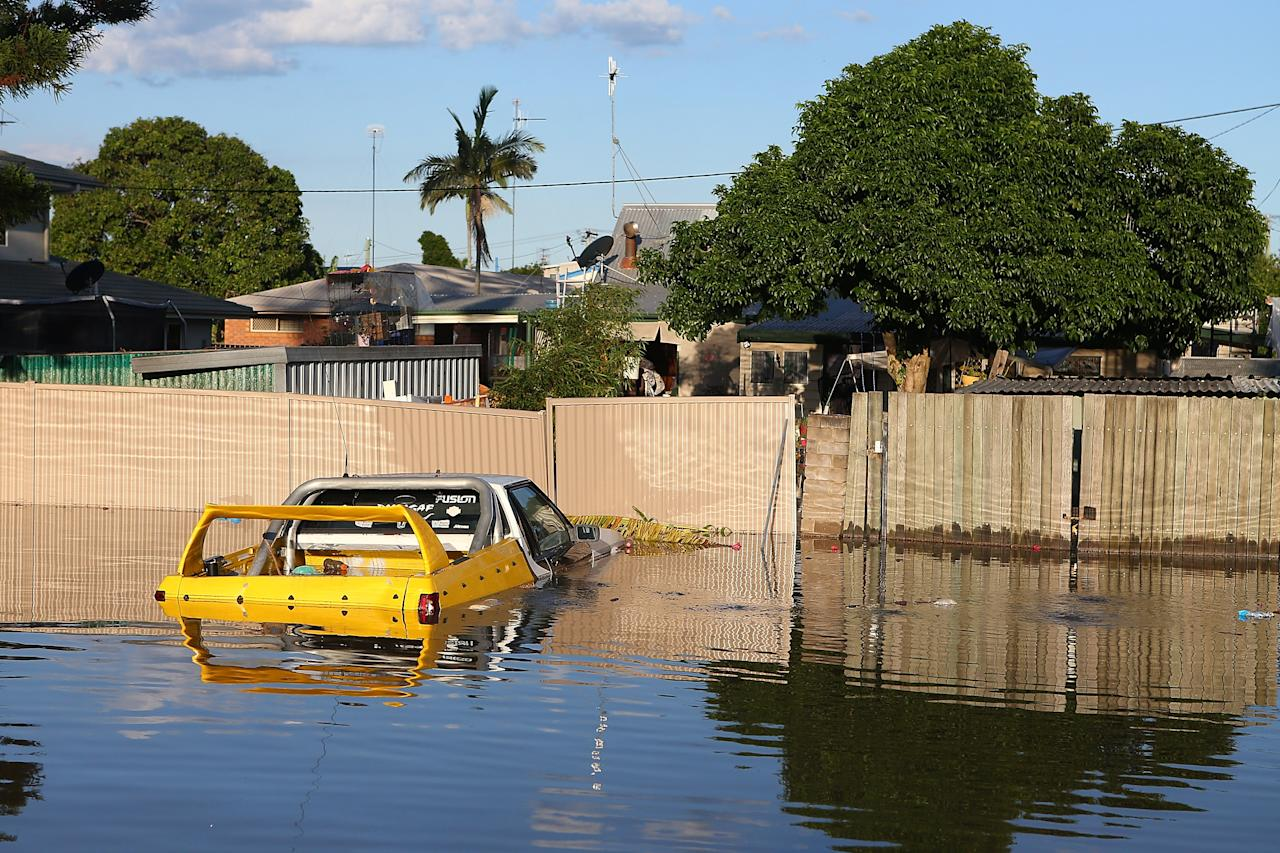 BUNDABERG, AUSTRALIA - JANUARY 29: A car floats in a flooded street as parts of southern Queensland experiences record flooding in the wake of Tropical Cyclone Oswald on January 29, 2013 in Bundaberg, Australia.Four deaths have been confirmed and thousands have been evacuated in Bundaberg as the city faces it's worst flood disaster in history. Rescue and evacuation missions continue today as emergency services prepare to move patients from Bundaberg Hospital to Brisbane amid fears the hospital could lose power. (Photo by Chris Hyde/Getty Images)