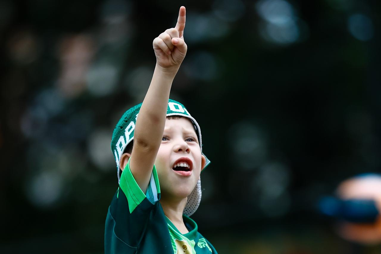 <p>An excited young fan salutes the team </p>