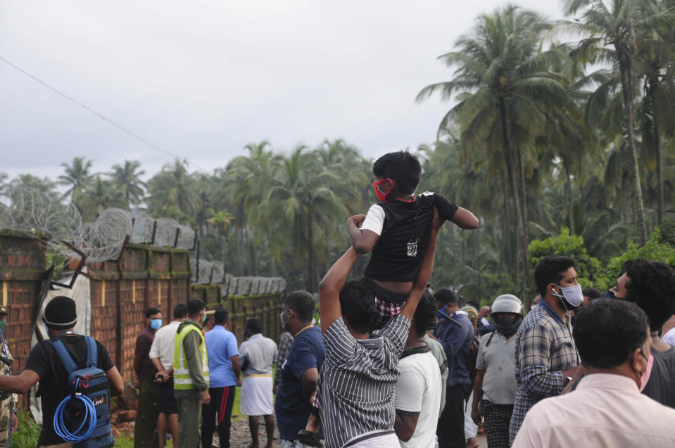 People gather to look at the Air India Express flight that skidded off a runway while landing at the airport in Kozhikode, Kerala state, India, Saturday, Aug. 8, 2020. The special evacuation flight bringing people home to India who had been trapped abroad because of the coronavirus skidded off the runway and split in two while landing in heavy rain killing more than a dozen people and injuring dozens more. (AP Photo/C.K.Thanseer)