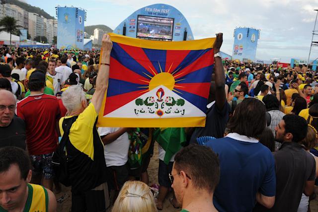 Supporters hold a Tibet flag at the Fan Fest in Rio de Janeiro