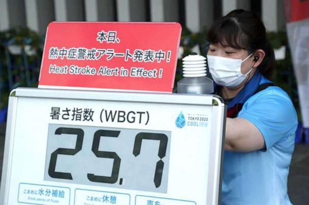 PHOTO: A woman attaches a heat warning sign at the Nippon Budokan martial arts hall on 26 July 2021 in Tokyo. (Friso Gentsch/dpa via Newscom)