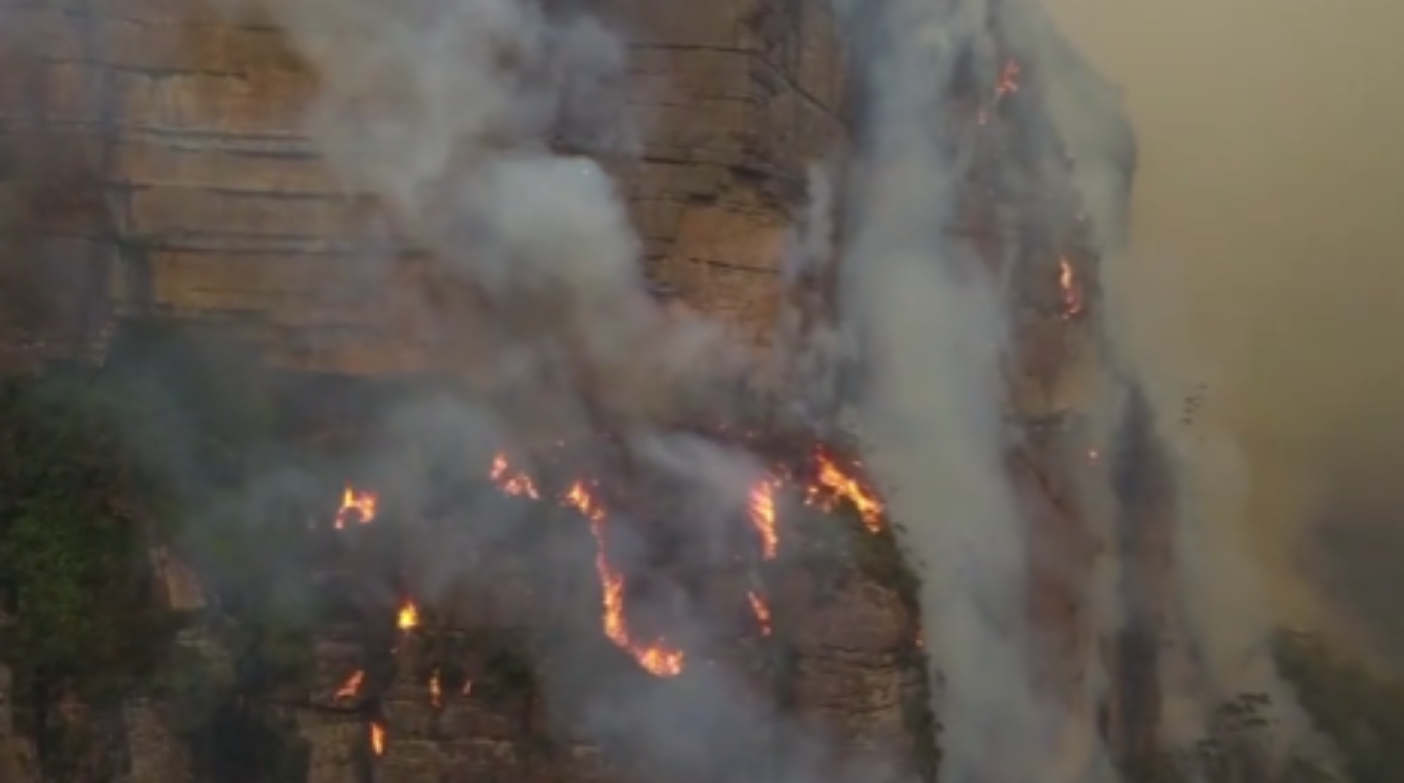 Fire can be seen tumbling down the side of a mountain as bushfires continue to sweep across Australia. (Caters)