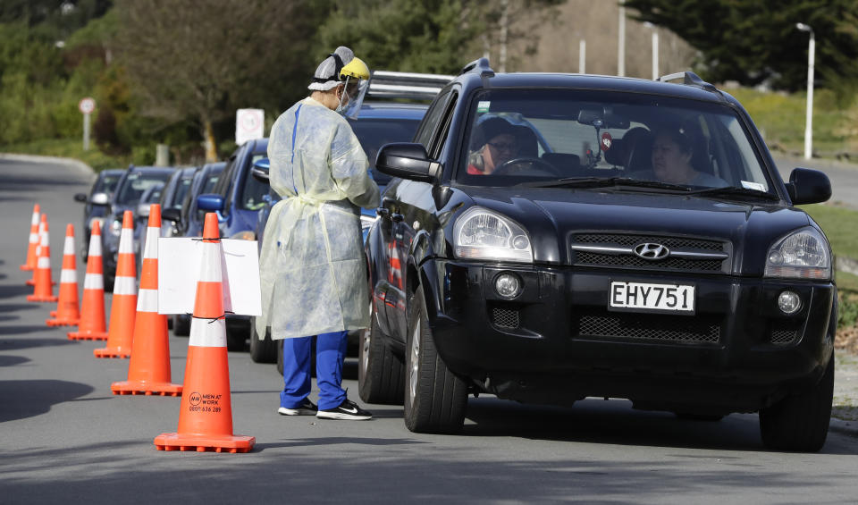 Medical staff prepare take a COVID-19 test from a visitor to a drive through community based assessment centre in Christchurch, New Zealand, Thursday, Aug. 13, 2020.