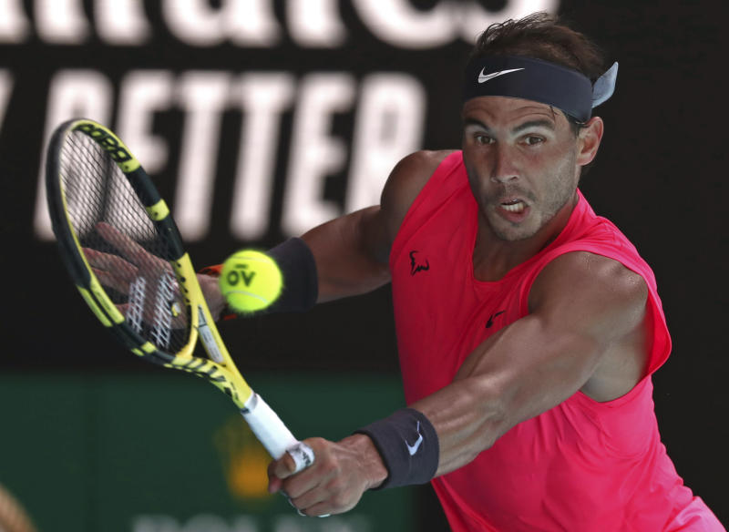 Spain's Rafael Nadal makes a backhand return to compatriot Pablo Carreno Busta during their third round singles match at the Australian Open tennis championship in Melbourne, Australia, Saturday, Jan. 25, 2020. (AP Photo/Dita Alangkara)