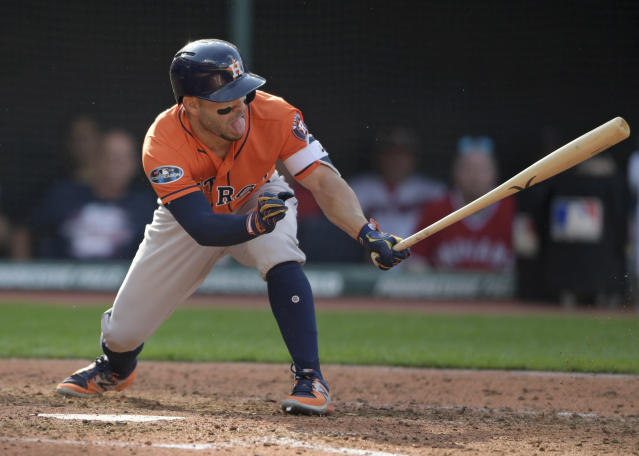 Houston Astros' Jose Altuve hits into a fielders choice in the seventh inning during Game 3 of a baseball American League Division Series against the Cleveland Indians, Monday, Oct. 8, 2018, in Cleveland. Tony Kemp scored on the play. (AP Photo/David Dermer)