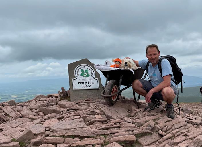 Carlos Fresco took his dying pet dog Monty up Pen y Fan in the Brecon Beacons on one last walk, pushing him in a wheelbarrow. (SWNS)