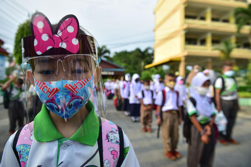 A student wears a face shield while observing social distancing as they line up to attend classes in a school in the southern Thai province of Narathiwat on July 1, 2020, as schools reopened after being temporarily closed due to the threat of the COVID-19 novel coronavirus. - Mask-wearing pupils returned to the courtyard of their schools on July 1, as Thailand pushed towards some sense of normality with the coronavirus largely in check. (Photo by Madaree TOHLALA / AFP) (Photo by MADAREE TOHLALA/AFP via Getty Images)