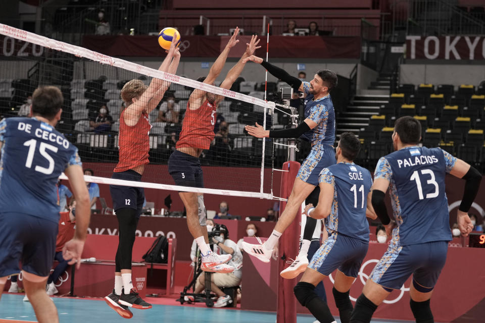 Argentina's Facundo Conte spikes a ball past Maxwell Holt, #12, and Taylor Sander, of the United States, during a men's volleyball preliminary round pool B match, at the 2020 Summer Olympics, early Monday, Aug. 2, 2021, in Tokyo, Japan. (AP Photo/Manu Fernandez)