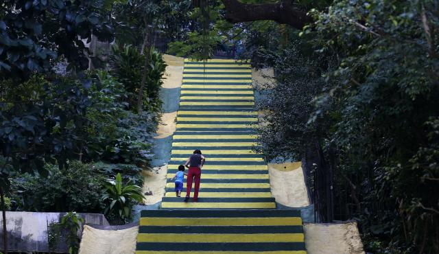 A woman walks with a child on stairs decorated in the Brazilian national soccer team's colours in celebration of the upcoming World Cup in Rio de Janeiro May 21, 2014. Rio de Janeiro is one of the host cities for the 2014 World Cup in Brazil. REUTERS/Sergio Moraes (BRAZIL - Tags: SPORT SOCCER WORLD CUP)