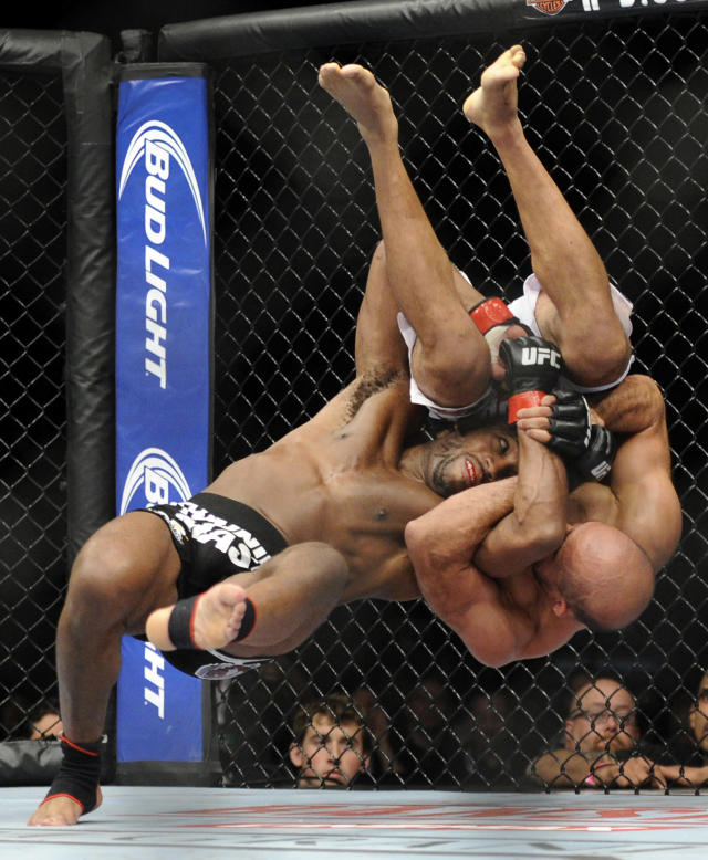 John Howard, left, takes down Slyar Bahadurzada during their UFC 168 mixed martial arts welterweight fight on Saturday, Dec. 28, 2013, in Las Vegas. Howard won by unanimous decision. (AP Photo/David Becker)