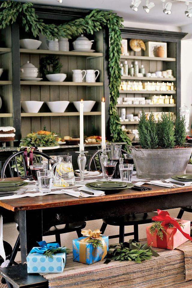 """<p>A long table features an unexpected centerpiece of live miniature trees and dried rose hips in a galvanized tub. Bright gifts serve as place cards, and lush garlands line exposed shelves.</p><p><a href=""""https://www.amazon.com/s/ref=nb_sb_noss?url=search-alias%3Dgarden&field-keywords=christmas+garland&tag=countryliving_auto-append-20&ascsubtag=[artid