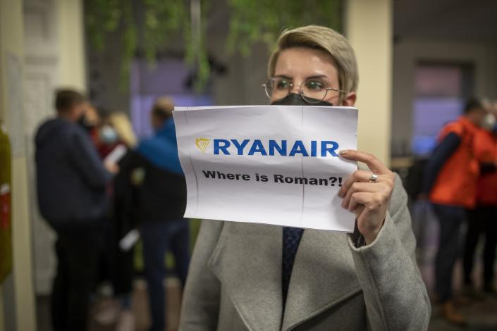 """A woman holds a poster reads """"where is Raman Pratasevich?!"""" as she waits to see passengers of the Ryanair plane with registration number SP-RSM, carrying opposition figure Raman Pratasevich which was traveling from Athens to Vilnius and was diverted to Minsk after a bomb threat, after its landing at the International Airport outside Vilnius, Lithuania, Sunday, May 23, 2021. The presidential press service said President Alexander Lukashenko personally ordered that a MiG-29 fighter jet accompany the Ryanair plane carrying opposition figure Raman Pratasevich and traveling from Athens, Greece, to Vilnius, Lithuania to the airport in the capital Minsk. (AP Photo/Mindaugas Kulbis)"""